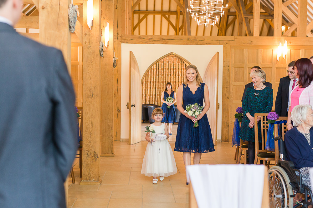 bridesmaid and flower girl walking down the aisle at Rivervale Barn wedding