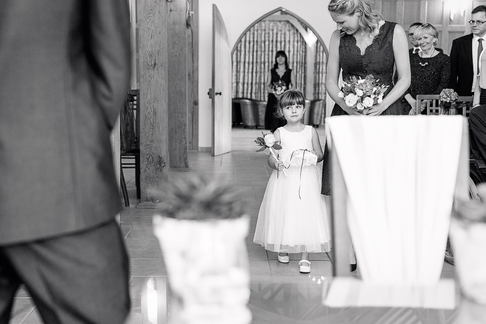 Flower girl carries wedding rings into ceremony