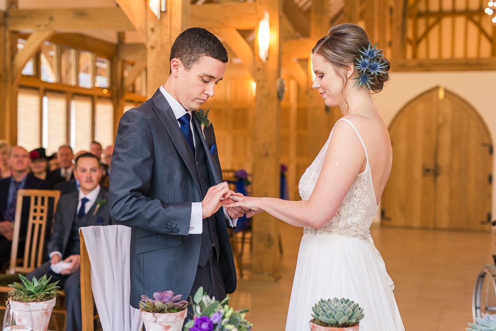 Bride and Groom exchange rings at Rivervale barn