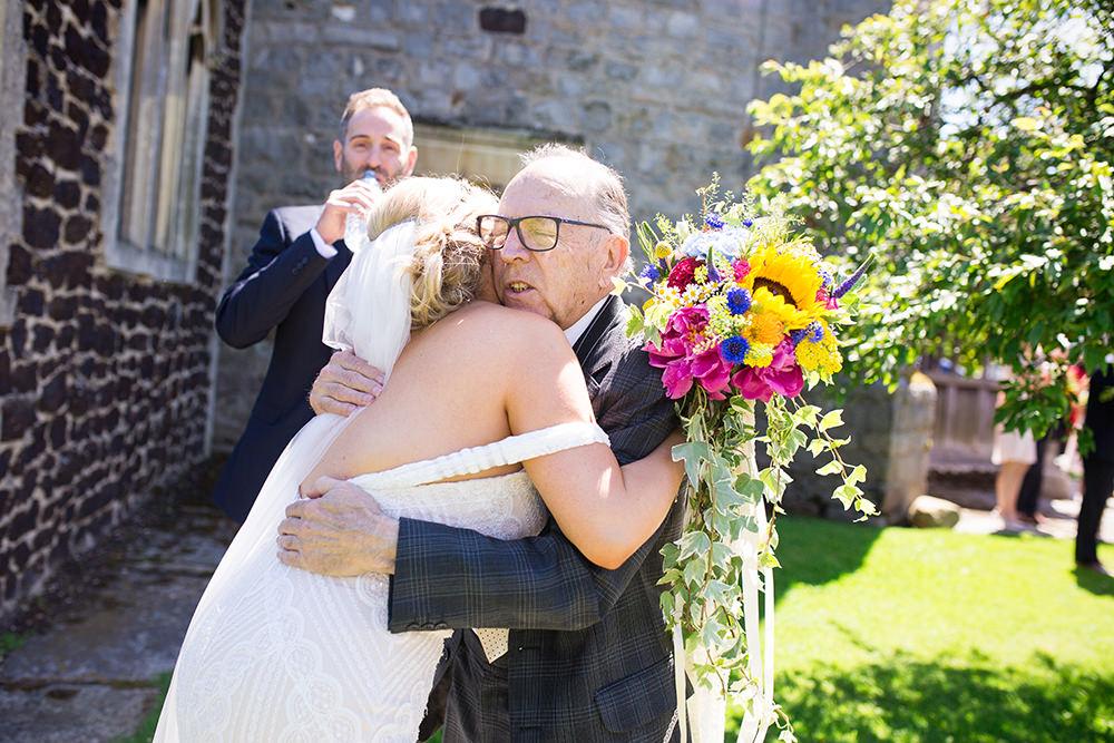 Bride hugs Grandad after wedding ceremony