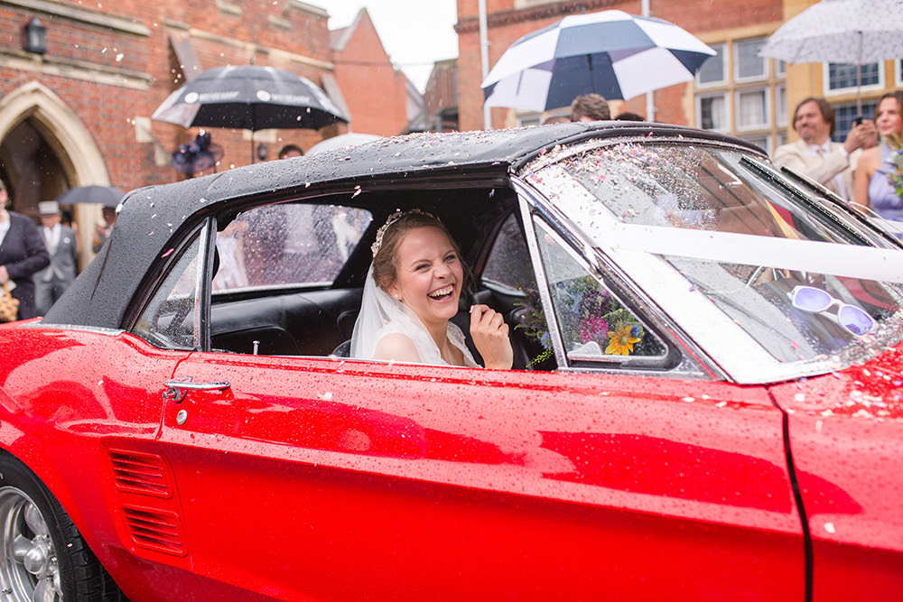 Bride in old Ford Mustang on wedding day